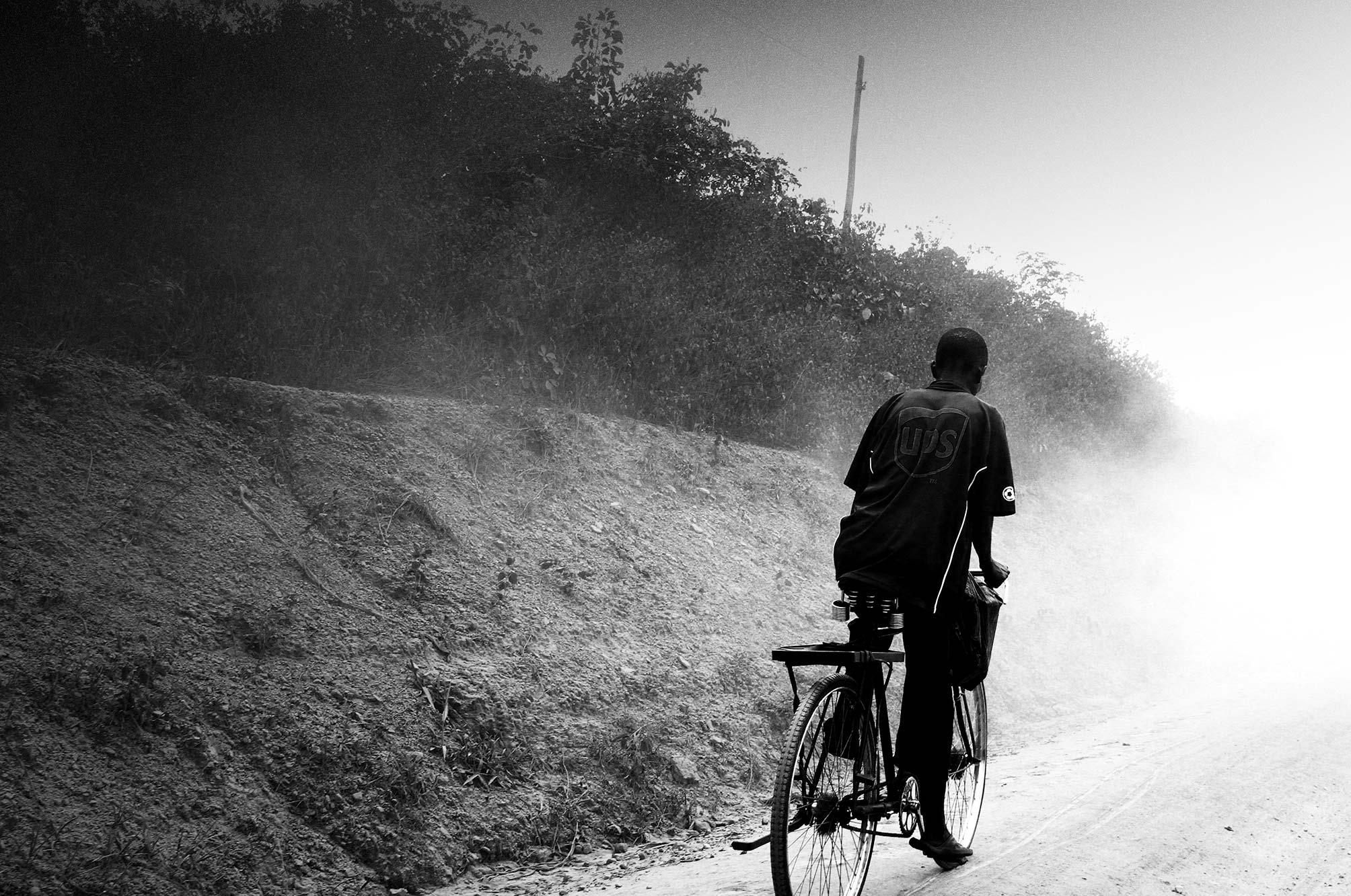Uganda man on bicycle with UPS shirt on