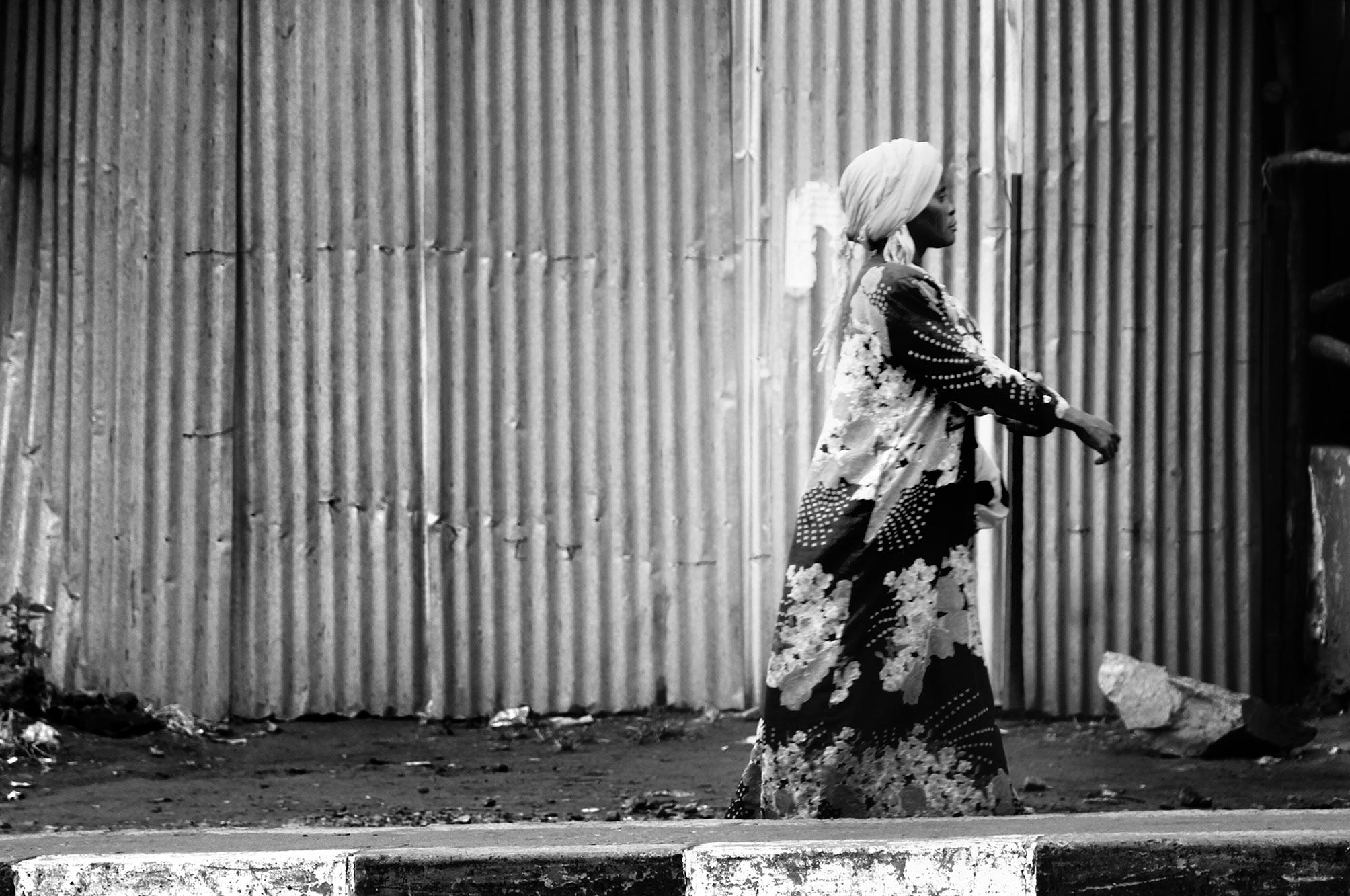 Uganda lady walking against corrugated fence
